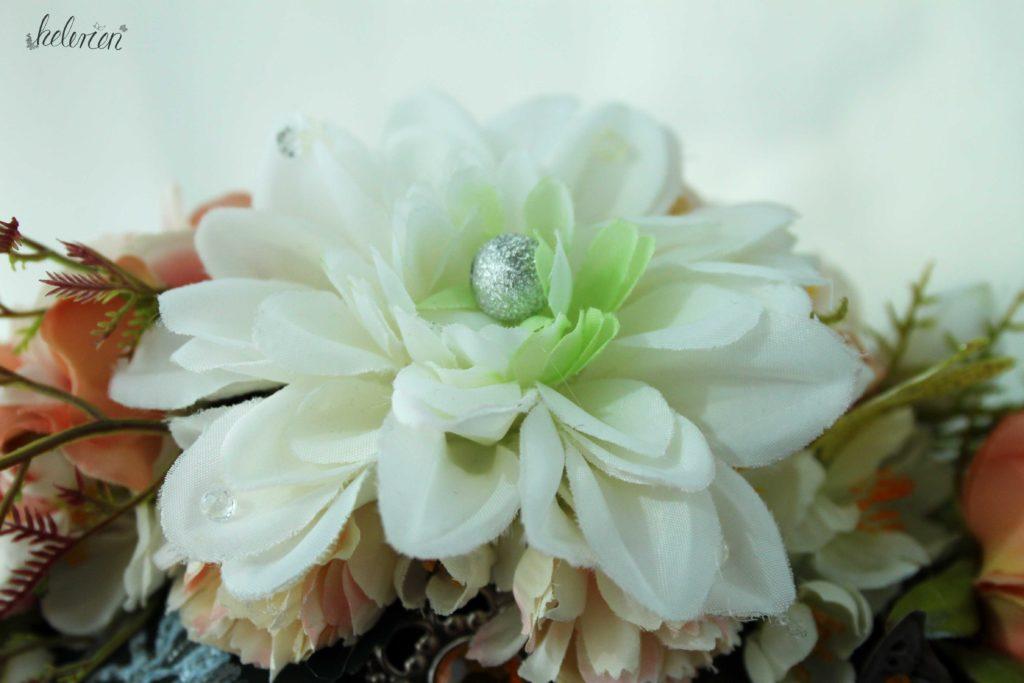 Blume oben auf dem Headpiece, verziert mit einer großen Perle in der Mitte und kleinen Kristallen auf einzelnen Blütenblättern