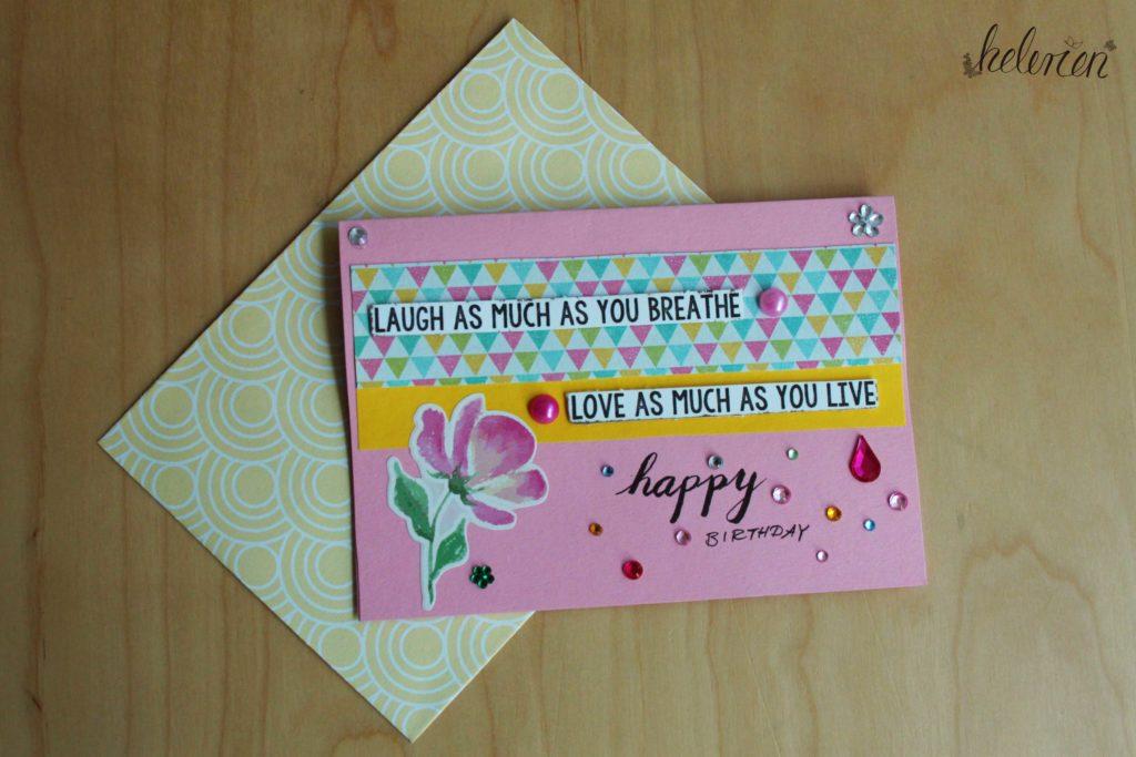"""rosa Karte mit einer Blume und dem Schriftzug Laugh as much as you breathe"""" und darunter Love as much as you live. viele Glitzersteine und ein happy birthday im unteren Drittel"""