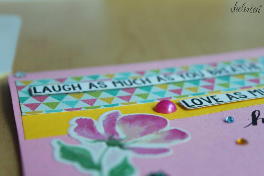 """rosa Karte mit einer Blume und dem Schriftzug Laugh as much as you breathe"""" und darunter Love as much as you live. viele Glitzersteine. Detailansicht"""