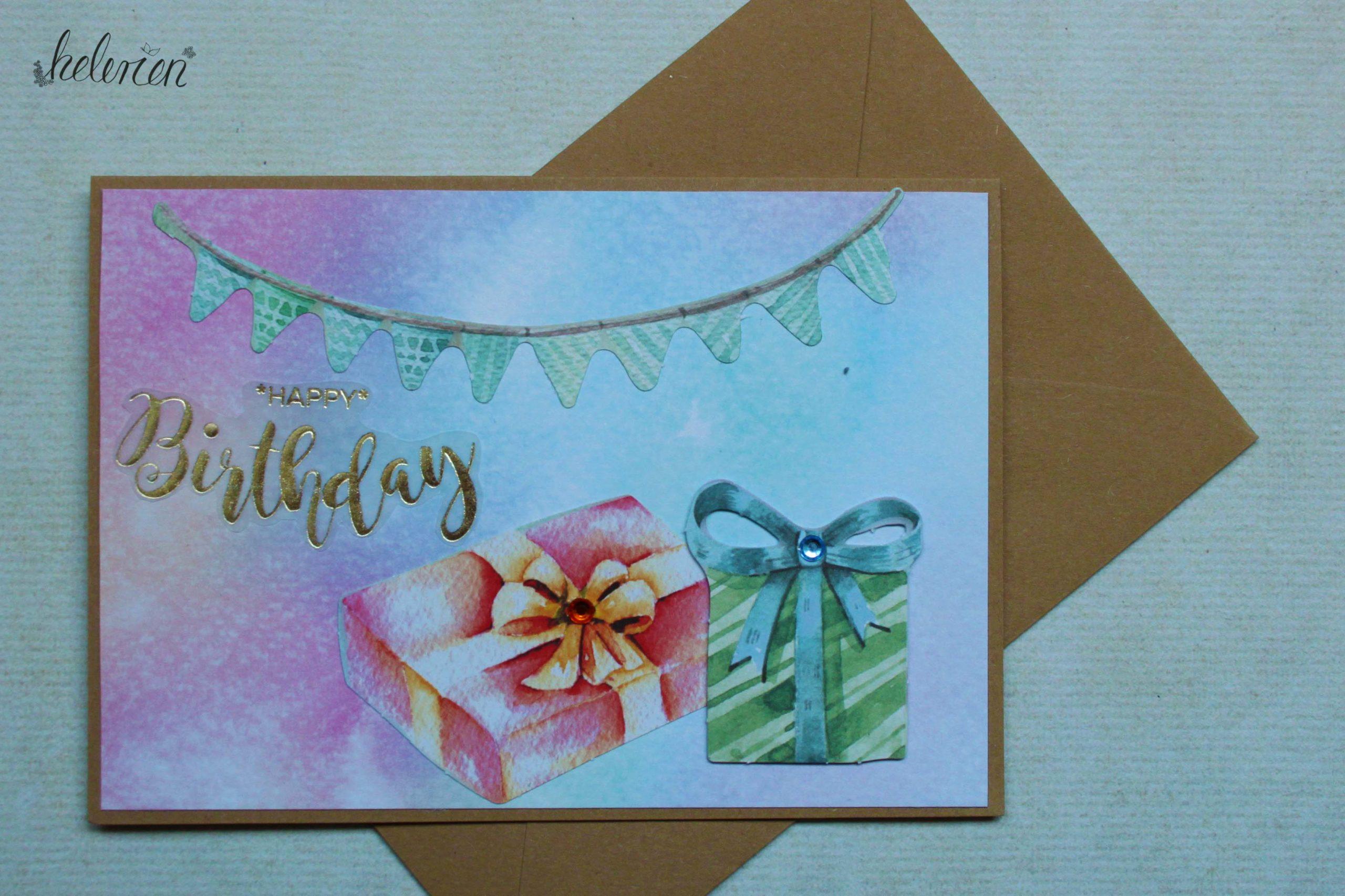 Karte mit Wasserfarbenhintergrund einer Wimpelkette oben und zwei Geschenken in der unteren rechten Ecke. ein goldener Happy Birthday Schriftzug i der linken Hälfte