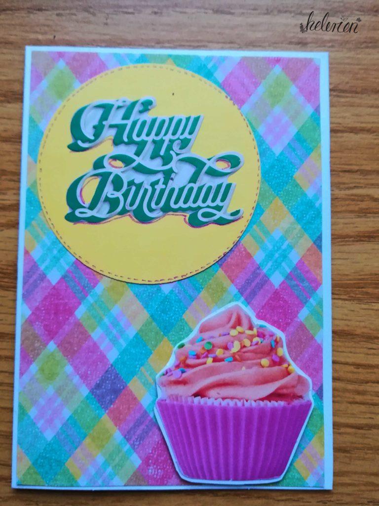 Karte mit buntem Karo Muster darauf ein Muffin unten rechts oben linsk ein geber kreis mit einem happy birthday sricker darauf