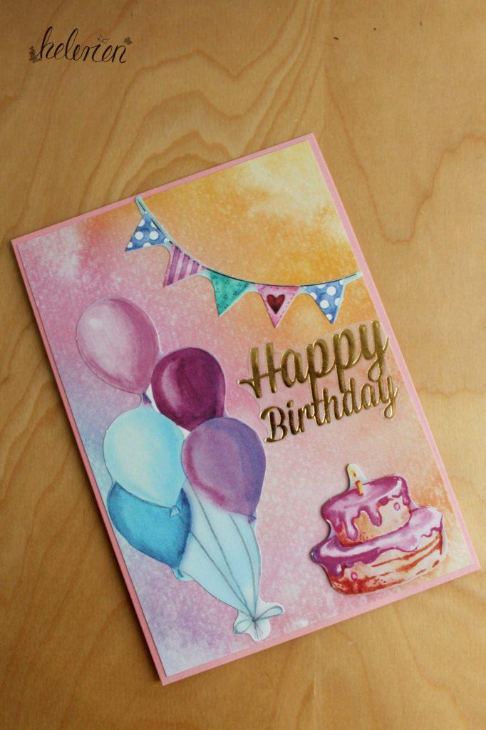 eine rosa Karte mit rosa orangenem Wasserfarben Hintergrund darauf linsk unten uftballons oben rechts eien Wimpelkette und unten rechts eine Torte. Zwischen Torte und Kette ein goldener Happy Birthday Schriftzug