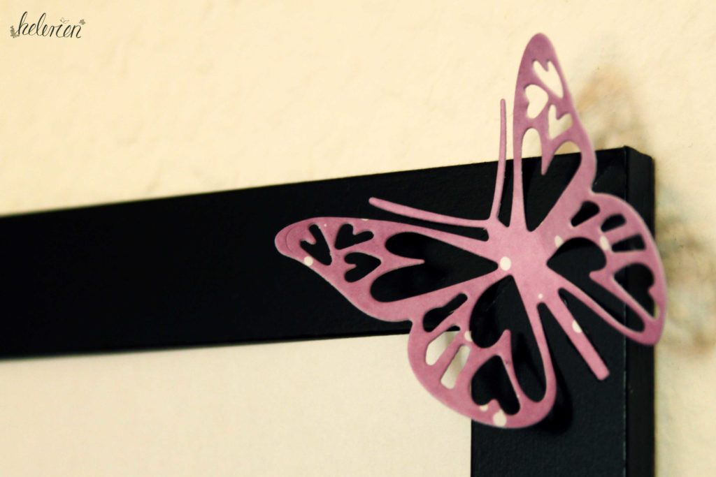 lilaner ausgestanzter Schmetterling am Bilderrahmen