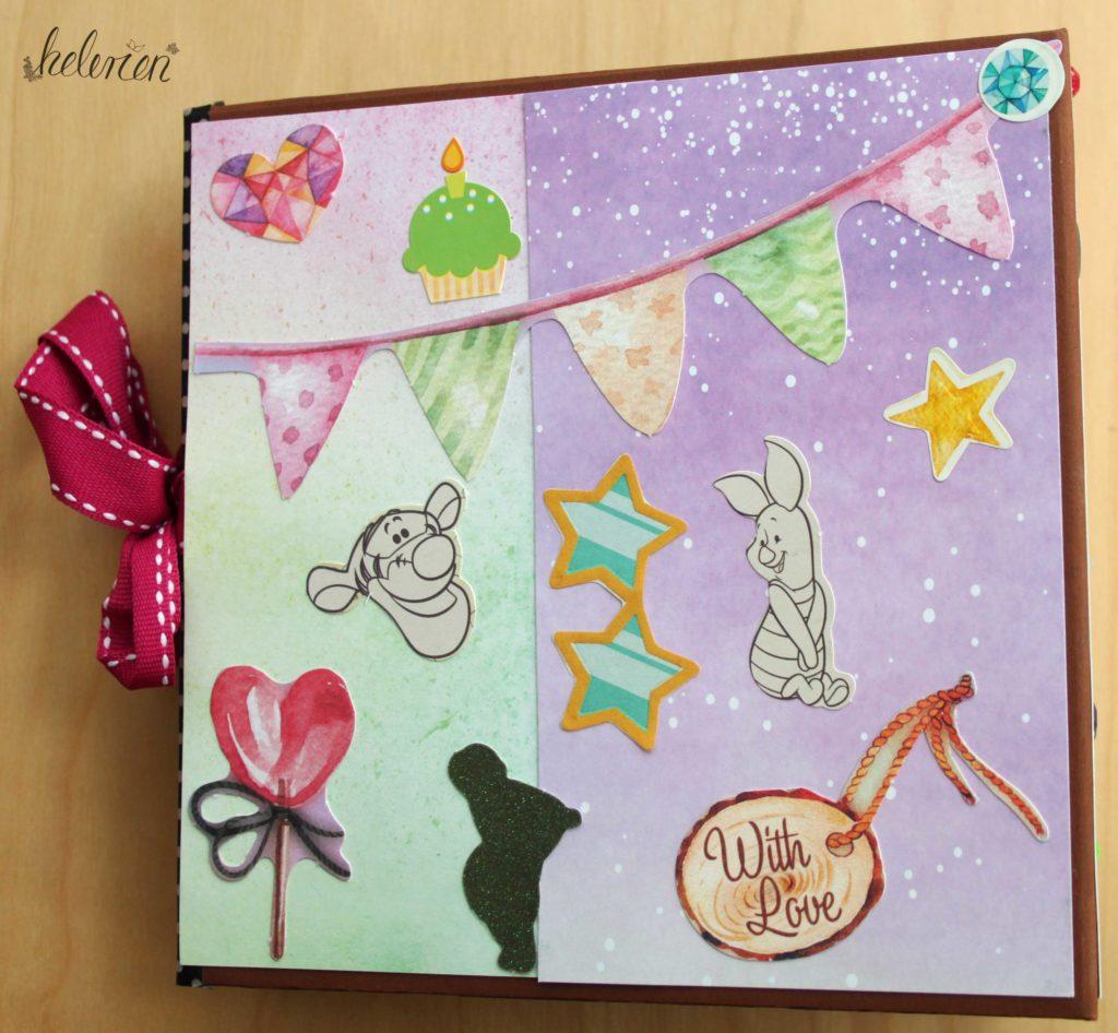 Das Backcover in lila und grünlichen Tönen mit Winnie Pooh Charakteren und einer große Wipelkette quer rüber außerdem Sterne, ein Herzlolli, Herzchen, ein Cupcake und ein Holzschild mit with love schrift