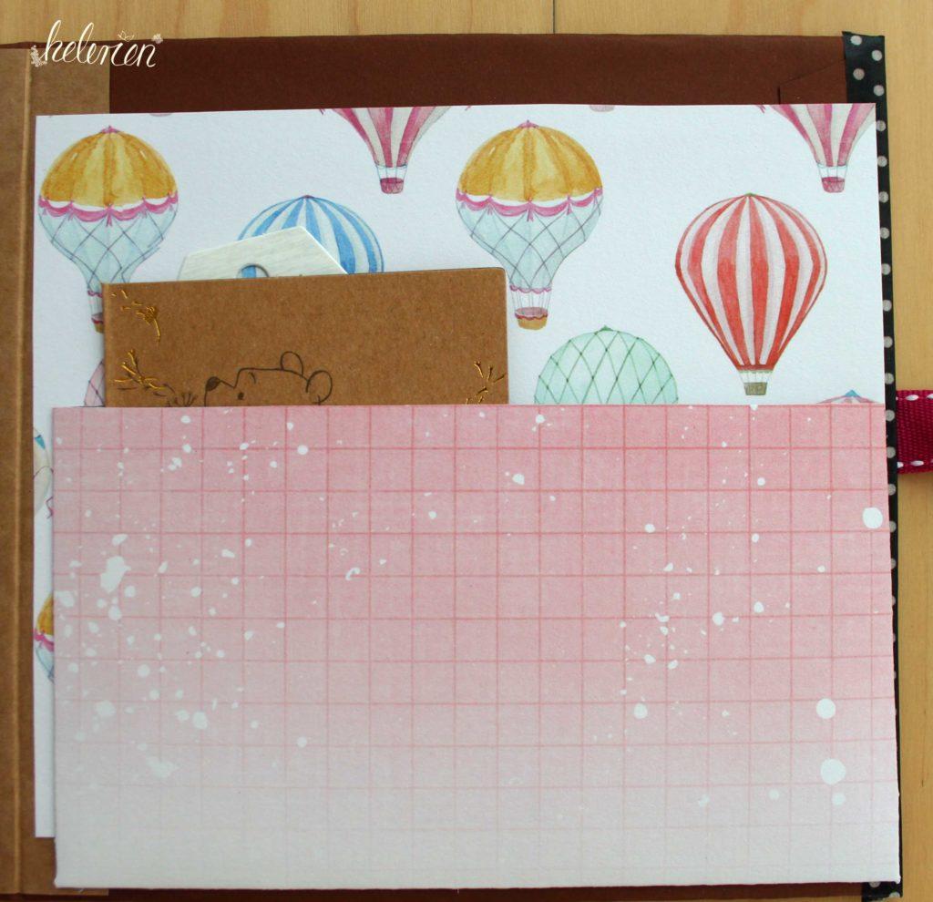 Tasche aus Papier mit risa-weiß Verlauf und leichtem Kästchenmuster. Tasche it im BAckcover, darin steckt eien kleine bruane Karte. Der Hintergrund ist ein Papier mit Heißluftballons