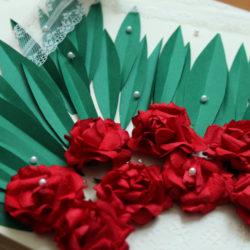 Cover mit roten Papierrosen, grünen Blättern, Perlen, Spitzenband und Tortenspitze im Detail